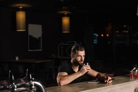 handsome man sitting at bar counter and drinking whiskey