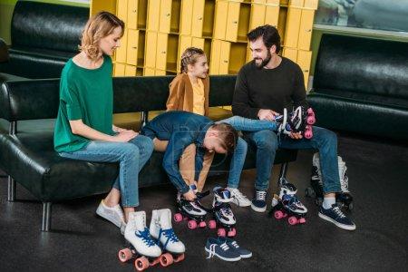 Photo pour Famille porter des patins à roulettes avant de patiner dans skate park - image libre de droit