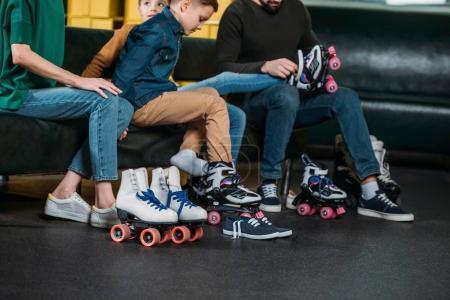 Photo pour Vue partielle de la famille porter des patins à roulettes avant de patiner dans skate park - image libre de droit