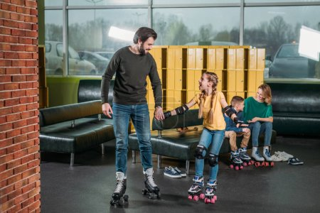 father and daughter going on roller rink to skate in skate park