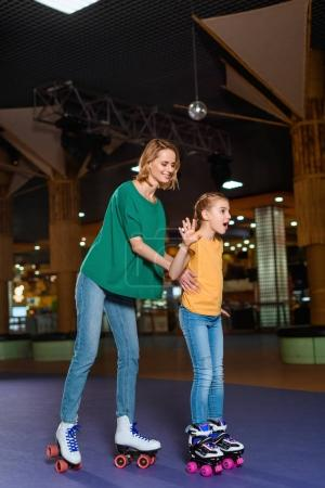 smiling mother and little daughter skating together on roller rink