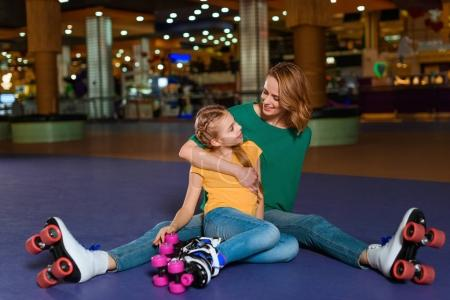 smiling mother and little daughter sitting on roller rink together