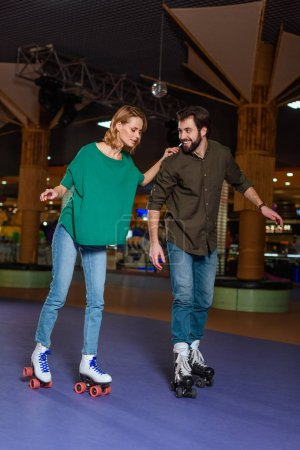 Photo for Young couple skating together on roller rink - Royalty Free Image