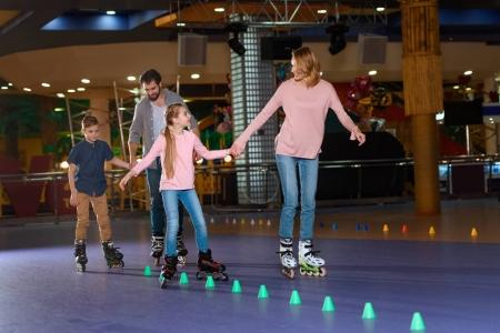 family spending time together on roller rink with cones