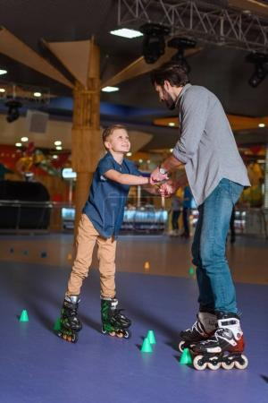 father and son skating together on roller rink with cones