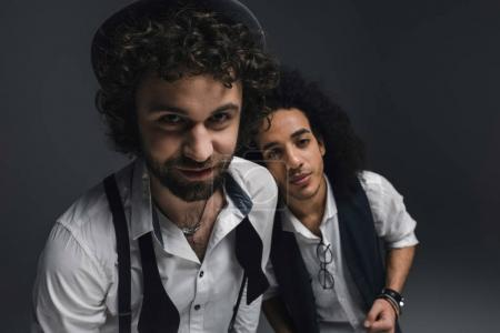 Photo for Close-up shot of happy stylish men looking at camera on black - Royalty Free Image