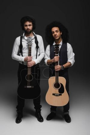 duet of handsome young musicians with acoustic guitars on black