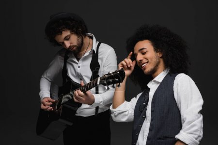 duet of musicians playing guitar and singing on black