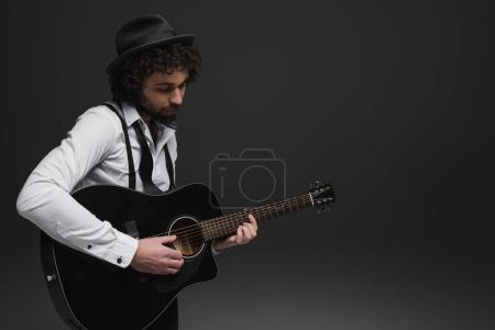 Photo for Handsome bearded musician playing acoustic guitar on black - Royalty Free Image