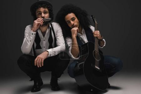 Photo pour Duo de musiciens avec guitare et harmonica assis anti-affaissement - image libre de droit