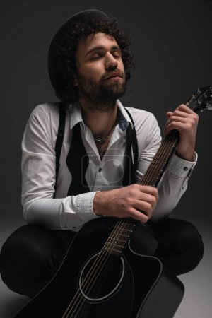young musician sitting on floor with acoustic guitar