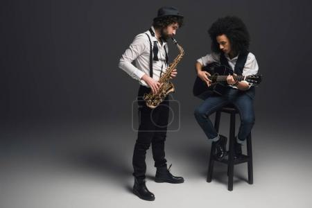 Photo for Stylish duet of musicians playing sax and acoustic guitar on black - Royalty Free Image