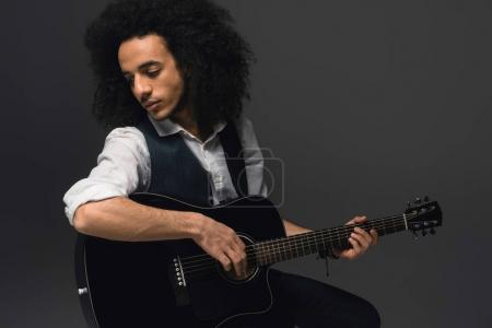 Photo for Handsome young musician playing acoustic guitar on black - Royalty Free Image