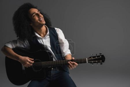 Photo for Artistic young musician playing acoustic guitar - Royalty Free Image