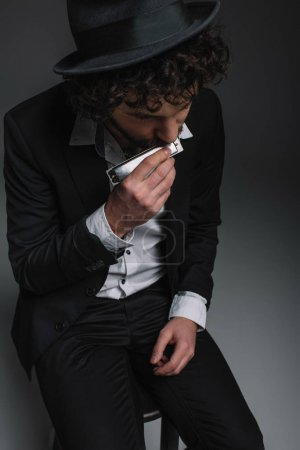 Photo for High angle view of handsome musician playing harmonica - Royalty Free Image