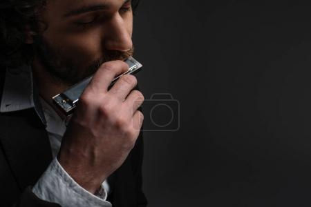 Photo for Close-up portrait of handsome musician playing harmonica on black - Royalty Free Image