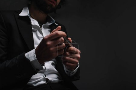 Photo for Cropped shot of musician in suit holding harmonica on black - Royalty Free Image