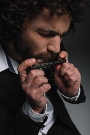 Photo for Close-up portrait of expressive young man playing harmonica on black - Royalty Free Image