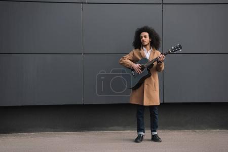 Photo pour Jeune musicien de rue jouant de la guitare à l'extérieur - image libre de droit