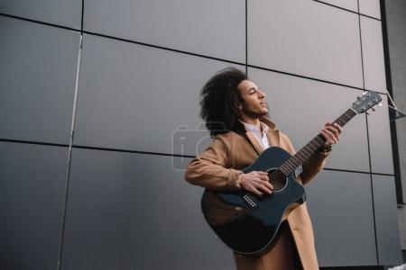 african american street musician playing guitar outdoors