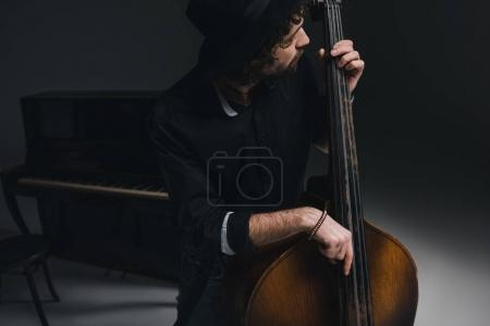 Photo for Young handsome musician playing contrabass - Royalty Free Image