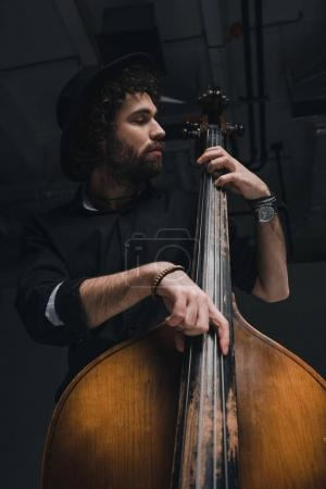 bottom view of handsome musician playing contrabass