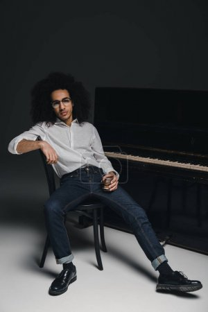 handsome stylish musician with glass of whiskey in front of piano