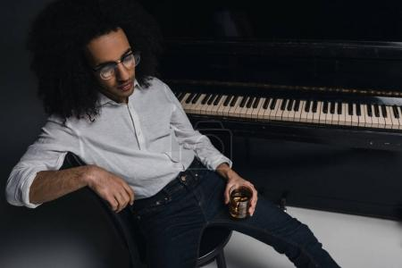 african american musician with glass of whiskey in front of piano