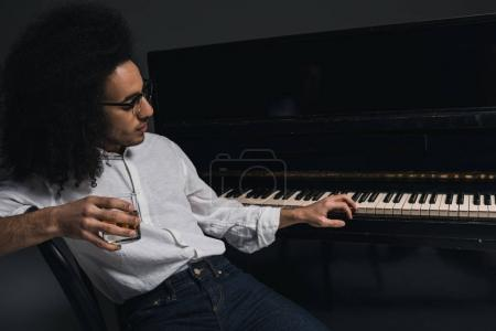 Photo for Handsome young musician drinking whiskey and playing piano on black - Royalty Free Image