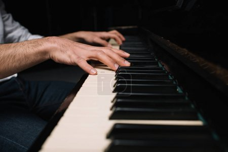 Photo for Cropped shot of man playing piano on black - Royalty Free Image