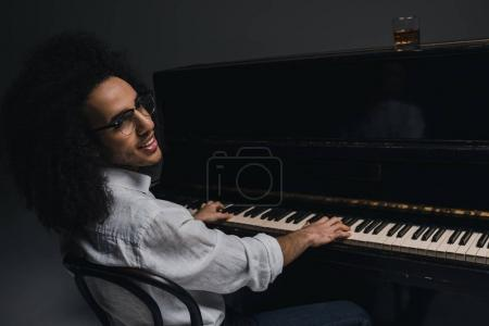 smiling young musician playing piano on black