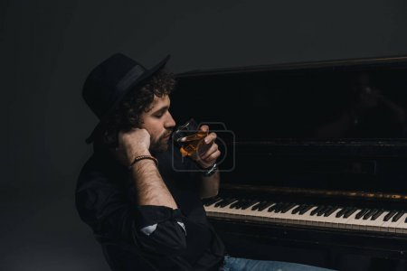 handsome musician drinking whiskey near piano on black