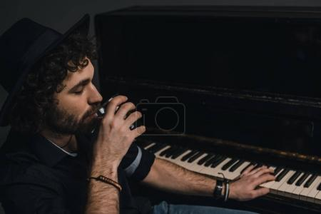 handsome musician drinking whiskey and playing piano