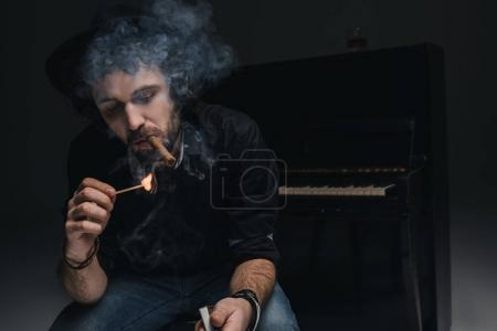 handsome bearded musician smoking cigar in front of piano on black