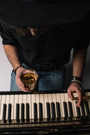 high angle view of musician with glass of whiskey and cigar playing piano