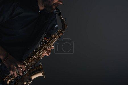 Foto de Toma recortada de jazzman tocar saxofón en negro - Imagen libre de derechos
