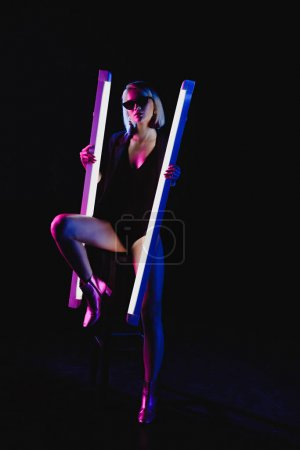 stylish beauty posing with two ultra violet lamps for fashion shoot, isolated on black