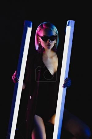 stylish girl posing with two ultra violet lamps for fashion shoot, isolated on black