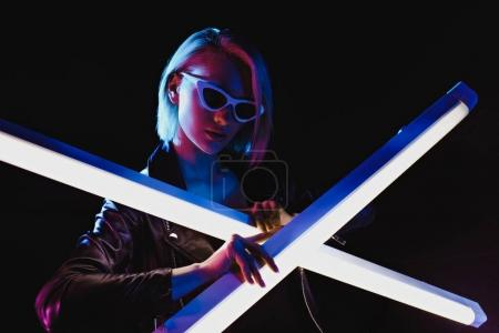 attractive girl posing with two ultra violet lamps for fashion shoot, isolated on black