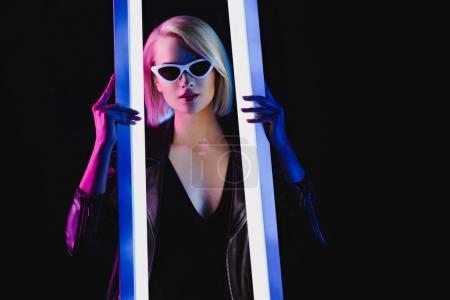 Photo pour Fille élégante posant avec deux lampes ultraviolettes, isolé sur noir - image libre de droit