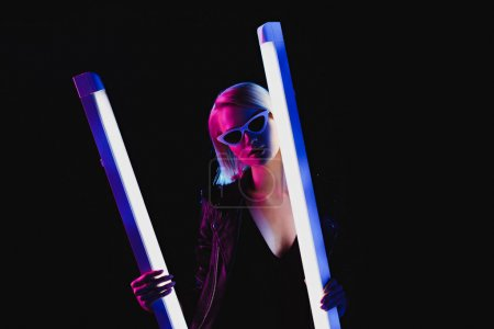 stylish girl posing with two ultra violet lamps, isolated on black