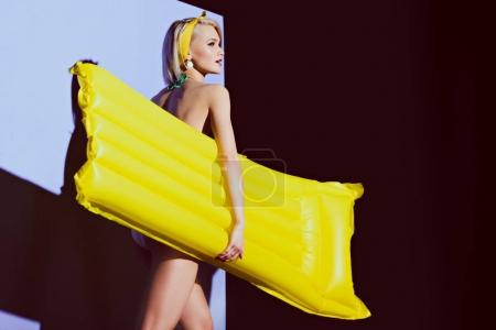girl posing with yellow inflatable mattress for fashion shoot