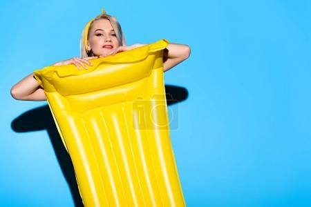 beautiful happy girl posing with yellow inflatable mattress on blue