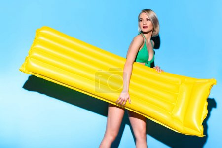 fashionable girl posing in bikini with inflatable mattress on blue