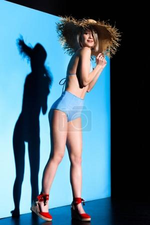 young girl posing in trendy bikini and straw hat on blue