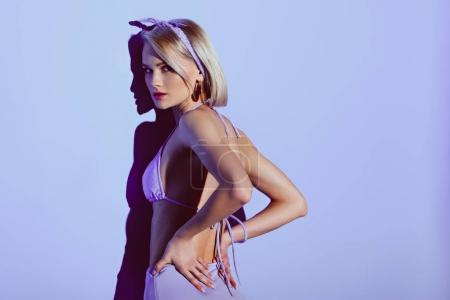 beautiful blonde girl posing in stylish bikini on purple