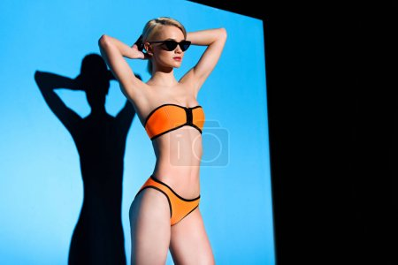 Photo for Stylish blonde girl posing in bikini and sunglasses on blue - Royalty Free Image