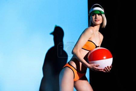 beautiful smiling girl posing in bikini and sun visor with beach ball on blue
