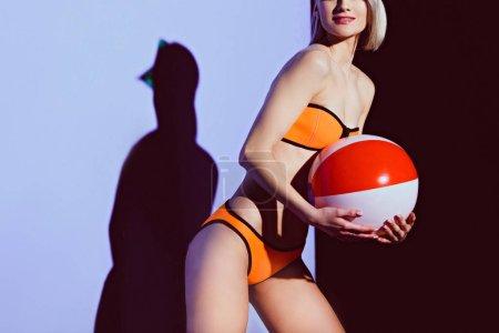 cropped view of girl in bikini and sun visor holding beach ball on purple