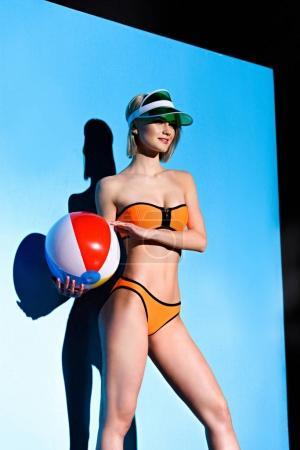 Photo pour Beau modèle élégant qui pose en bikini et sun visor avec ballon de plage sur bleu - image libre de droit